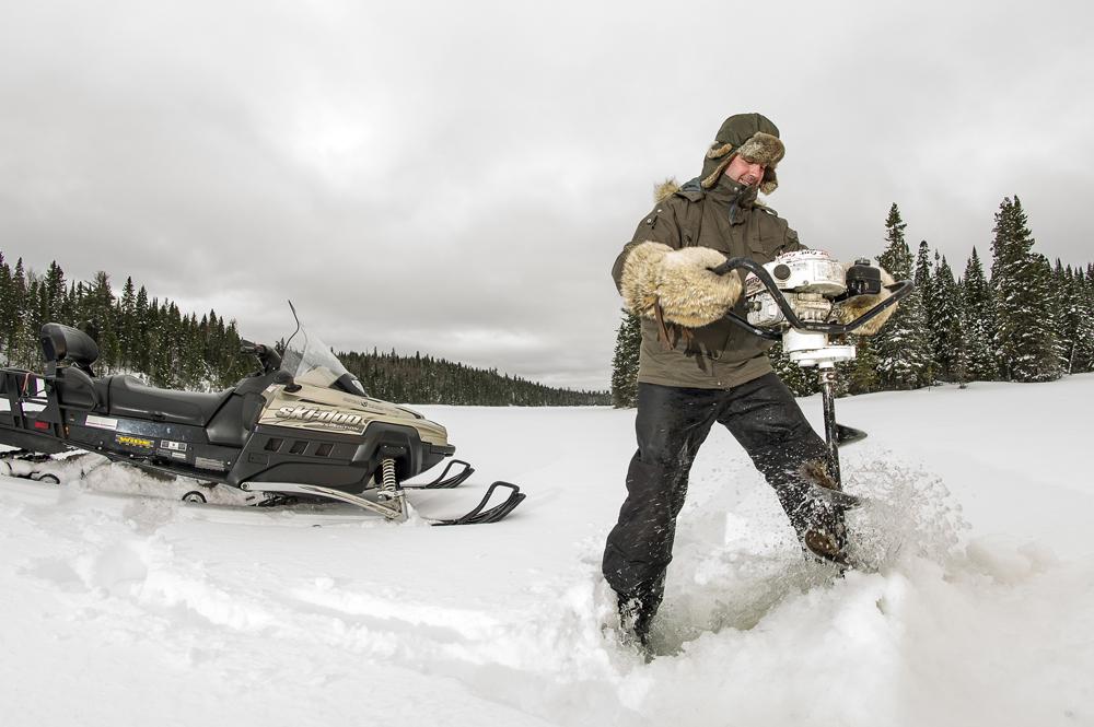 Photo couleur, un homme fait un trou sur un lac gelé à l'aide d'une terrière à gaz.