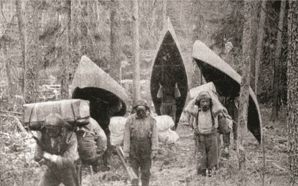 Black and white photo, several men carry canoes and baggage during a portage.