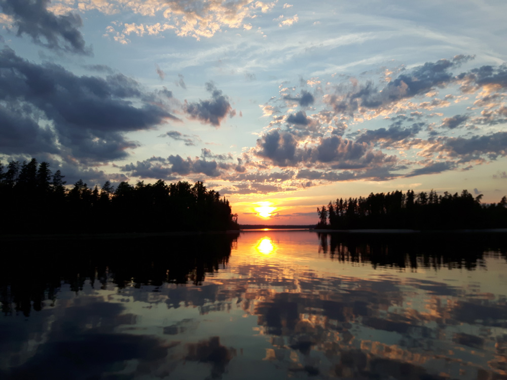 Colour photo of a sunset; the cloudy sky is reflected on the water's surface.