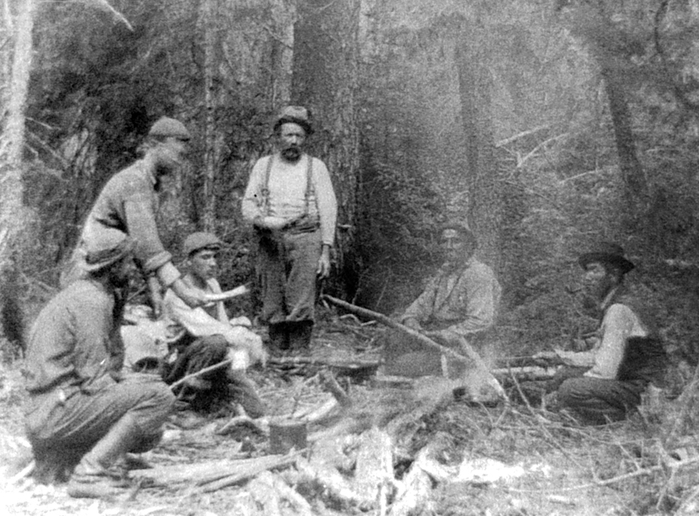 Black and white photo, six men gathered around a fire. Plates in hand, they are getting ready to enjoy a delicious meal prepared by their dedicated guides.