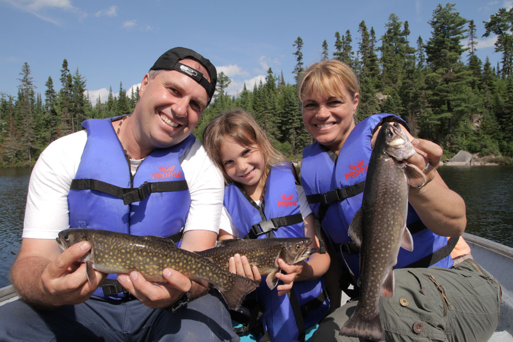 Colour photo, a family, father, mother and daughter, sitting in a rowboat, each holding a beautiful speckled trout