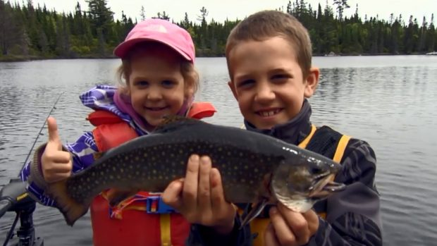 Two children, a boy and a girl proudly pose with a beautiful speckled trout in hand.
