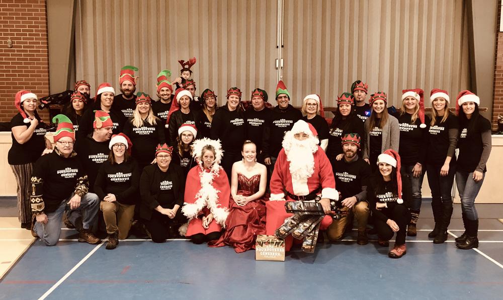 Photo couleur, un groupe posant fièrement lors d'une fête de Noël.