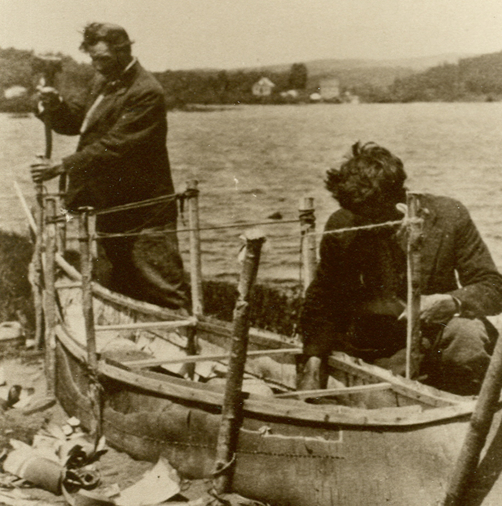 Sepia-toned photo, two men building a traditional birch bark canoe by the shoreline. A few pieces of bark cover the ground.
