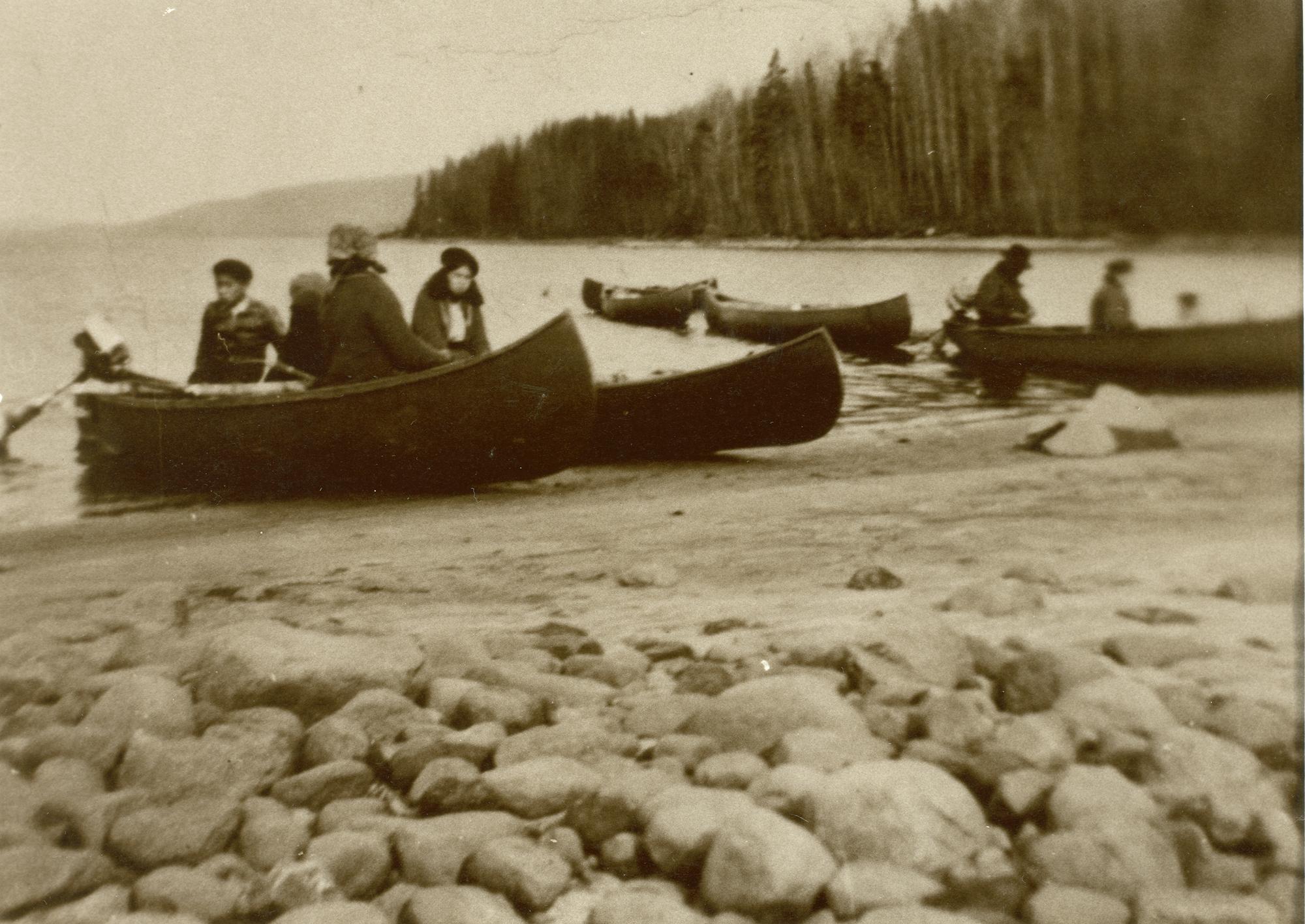 Photo en noir et blanc, quelques canots sur le bord du rivage.  Les personnes sont prêtes à partir à la pêche.