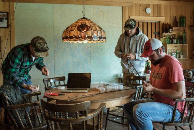 Colour photo, three men near a table preparing their rigging for a fishing trip.