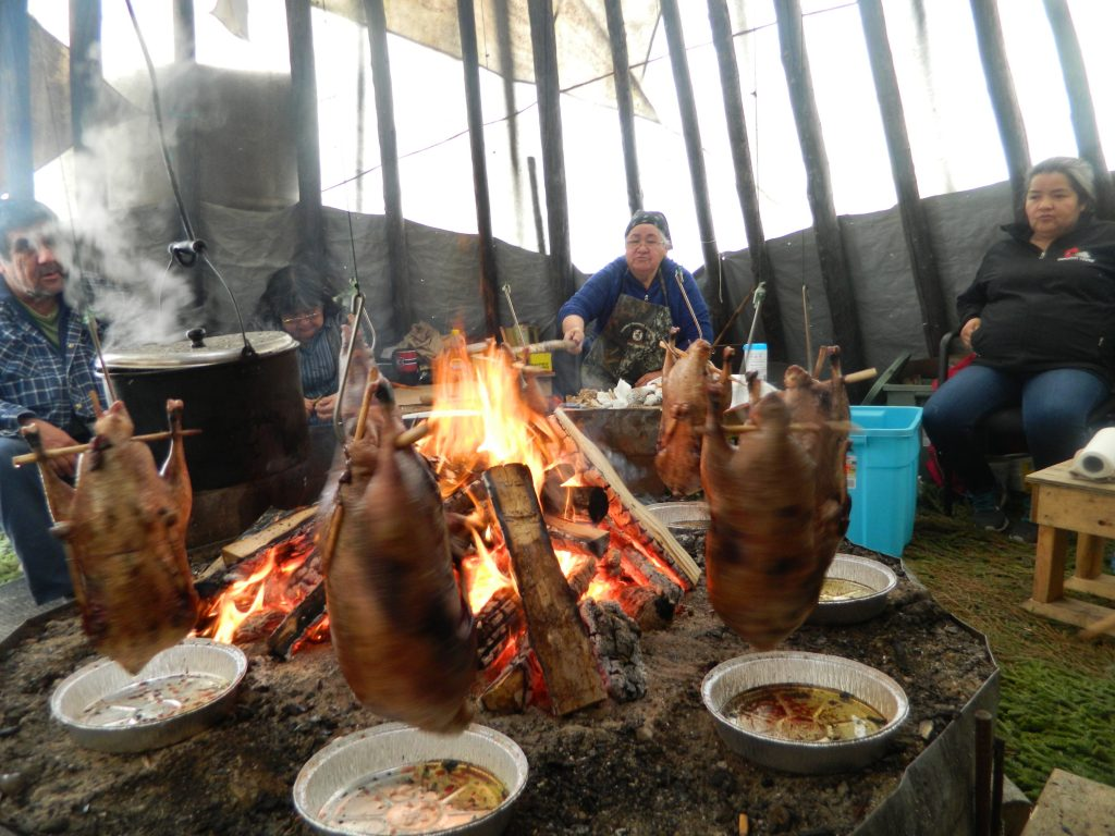 Three people sit behind the fire in a teepee. In the foreground, geese are suspended on cords for roasting.
