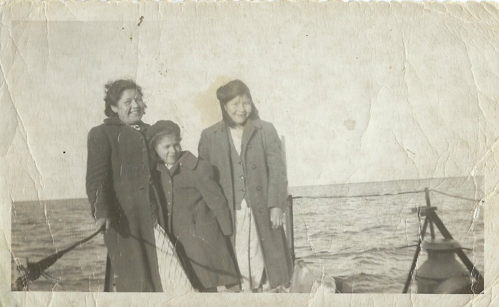 Three girls stand together at the back of a boat.