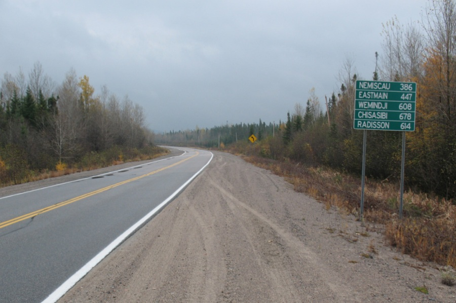 Highway through the forest and road sign showing distance to Cree towns.
