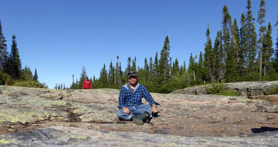 Man in blue checked flannel shirt and jeans sitting in sun on a big rock