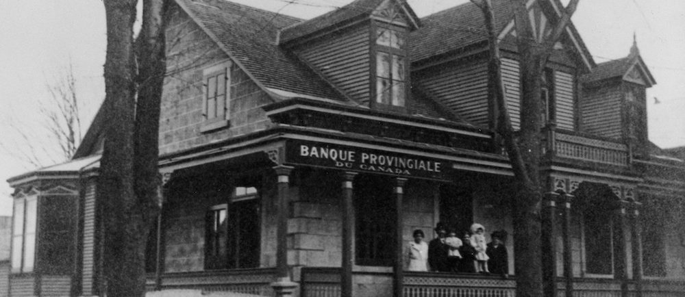 Black and white photo of an ancestral house. It served as a branch of the Provincial Bank of Canada. A family is standing on the front porch.