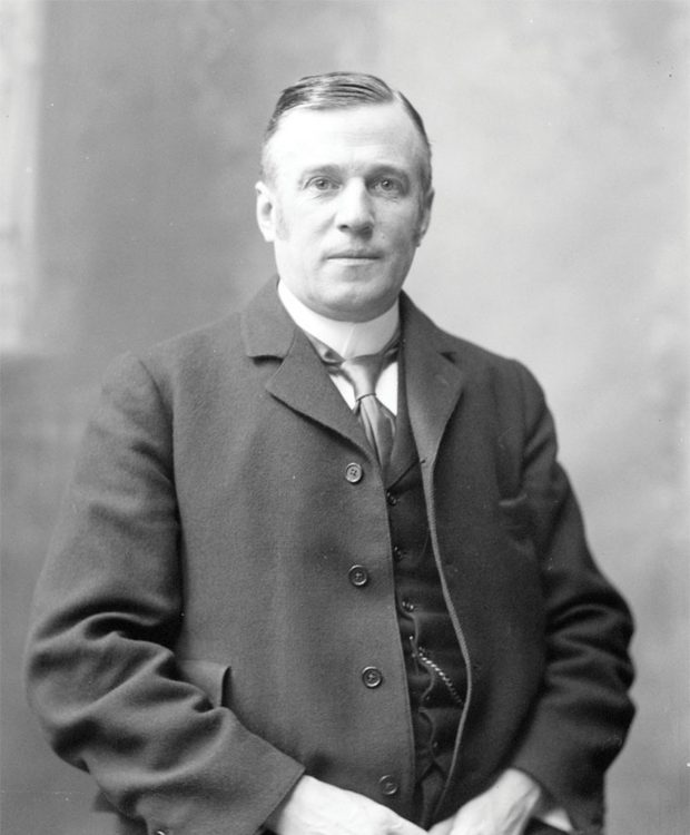A black and white portrait of Sir Joseph Pope, from head to hips, his arms folded in front of him, wearing a three-piece suit and tie, a watch chain and high collar. He is looking directly at the camera.