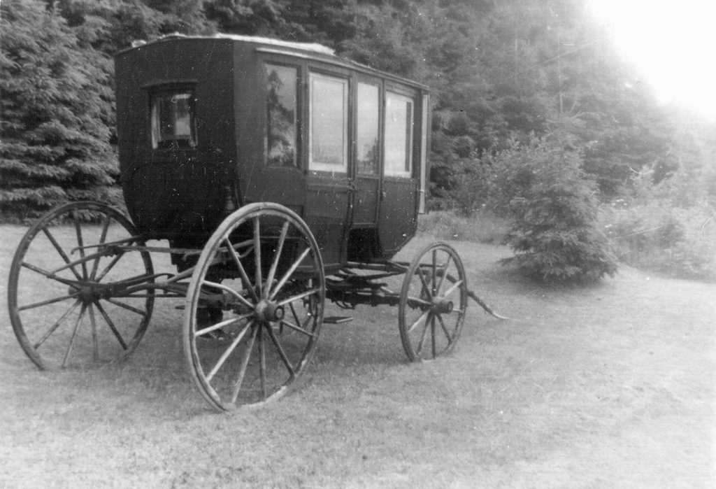 A black and white photograph of a one-horse carriage, with a covered roof and a door and windows on it, and four large wooden wheels. It is resting on a lawn with trees behind it.