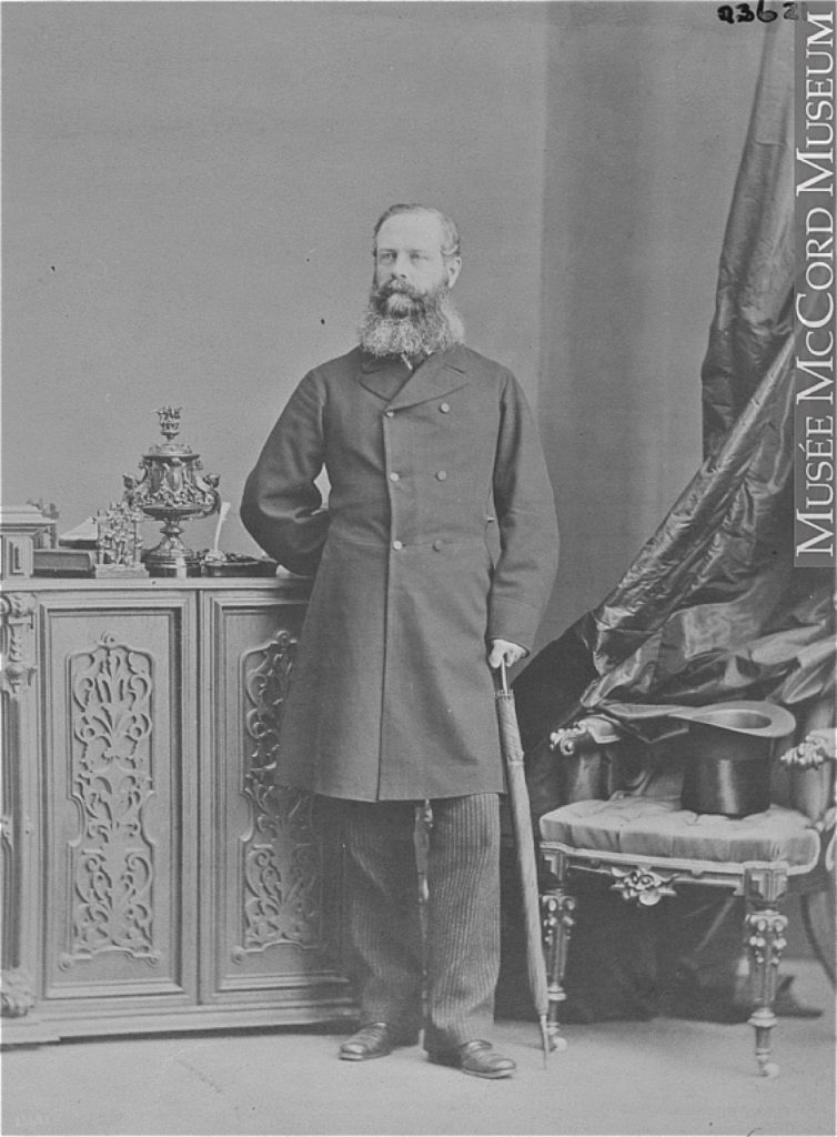 Black and white photograph of a man (Lord Monck) standing, leaning on a folded-up umbrella, his other hand held behind his back. There is a chair next to him on which sits a top hat. The man has a full beard and is dressed in a double-breasted woolen overcoat.