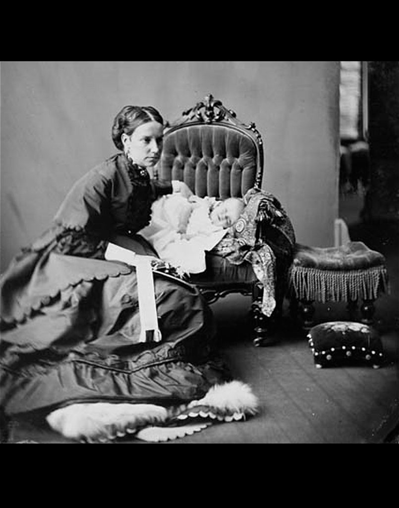 Lady Agnes Macdonald crouches next to a chair in which her baby Mary is propped, 1868.