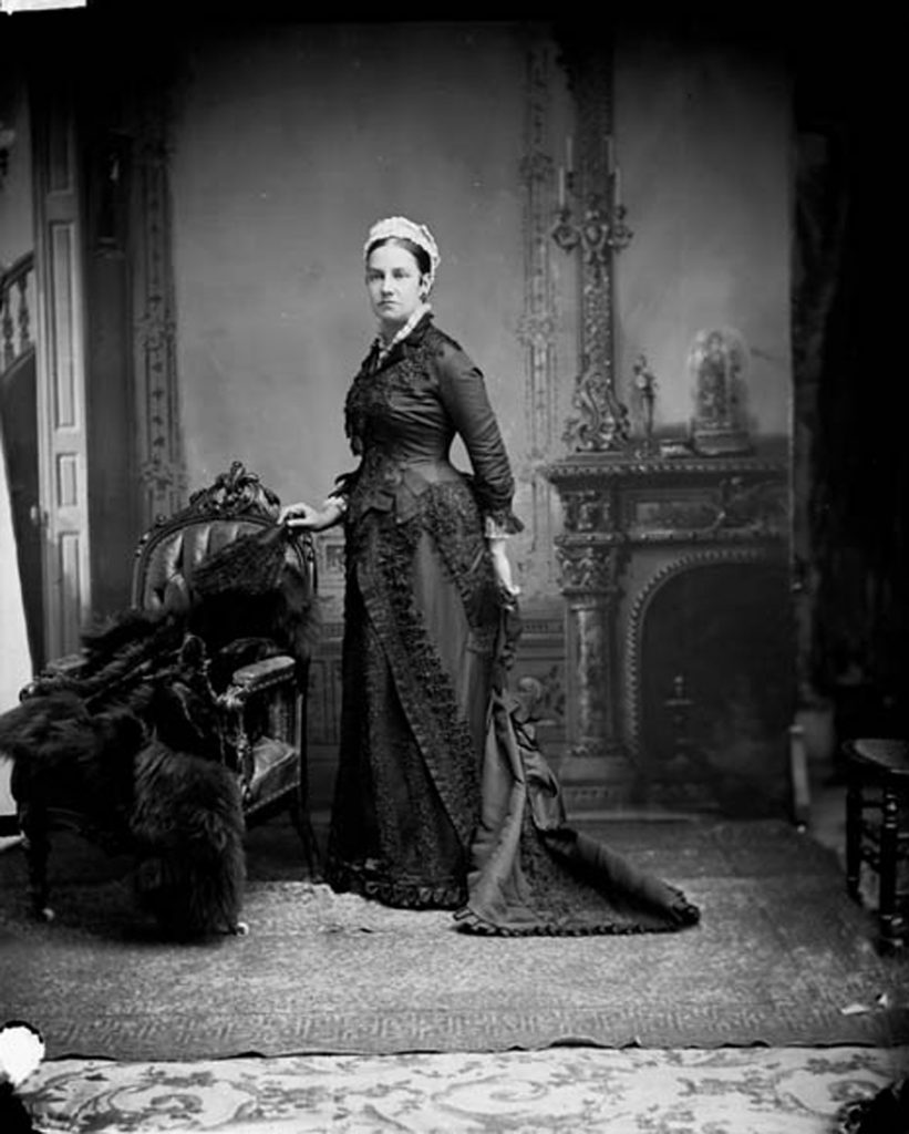Lady Agnes Macdonald dressed in a long black dress standing in front of a hearth, next to a fur coat which is draped over a chair.