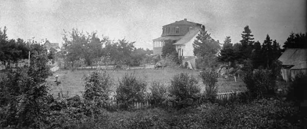 Black and white photo of summer home Villa Les Rochers, c. 1883, and partial grounds or front lawn, edged by evergreen trees. A wooden shed is in the right foreground and in the distance there is a peaked roof of the neighbouring cottage.