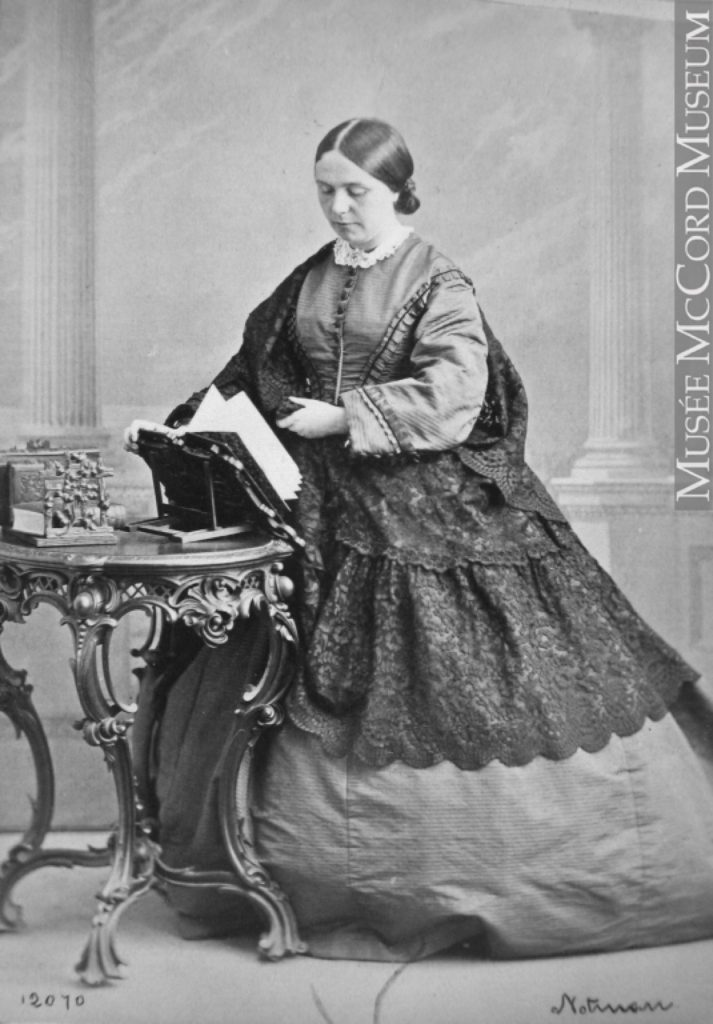 Black and white photo of a woman (Lady Frances Monck) standing, a wide full-length skirt draped with lace; she is turning the pages of a book which is open on a stand in front of her.