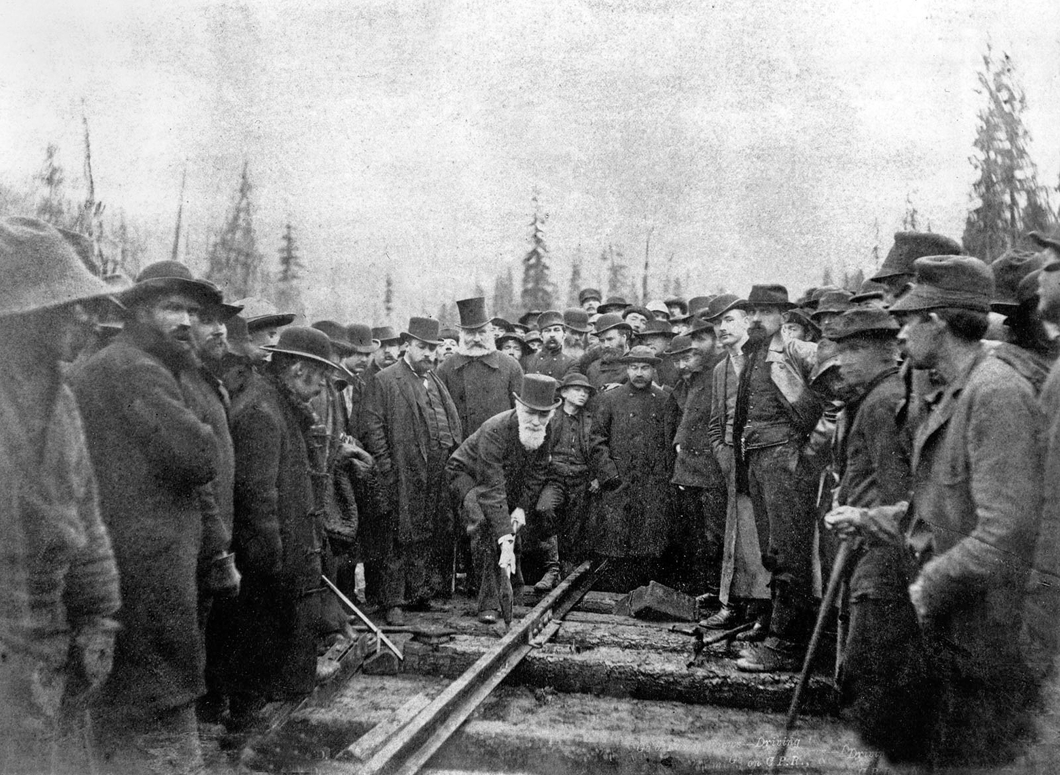A black and white photo taken in 1885, with over a hundred gentlemen in dark woolen suits surrounding one, Sir Donald A. Smith, who is poised above a piece of railroad track, wearing a top hat and holding a large hammer against the track, about to drive the last railroad spike for the Canadian Pacific Railway.