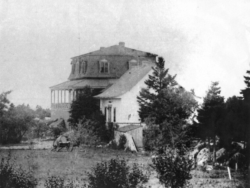Photo noir et blanc d'une bâtisse (la villa Les Rochers) constituée de deux parties: une maison de ferme simple à charpente triangulaire, agrandie d'une annexe dotée d'un toit en mansarde. Des arbres et des arbustes entourent la propriété.