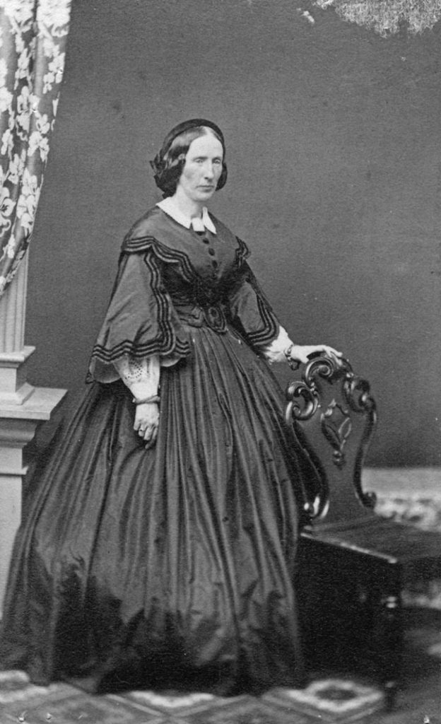 A formal black and white portrait of Louisa Macdonald, a woman standing in a full-length black dress, holding one hand on the back of a chair. Her dark hair is parted in the middle and arranged at the back. Her expression is distant and serious.