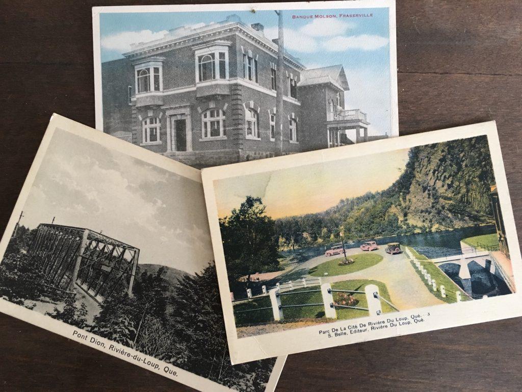Photographie de trois cartes postales anciennes, coloriées à la main, se chevauchant sur une table, chacune illustrant différents paysages de Rivière-du-Loup.