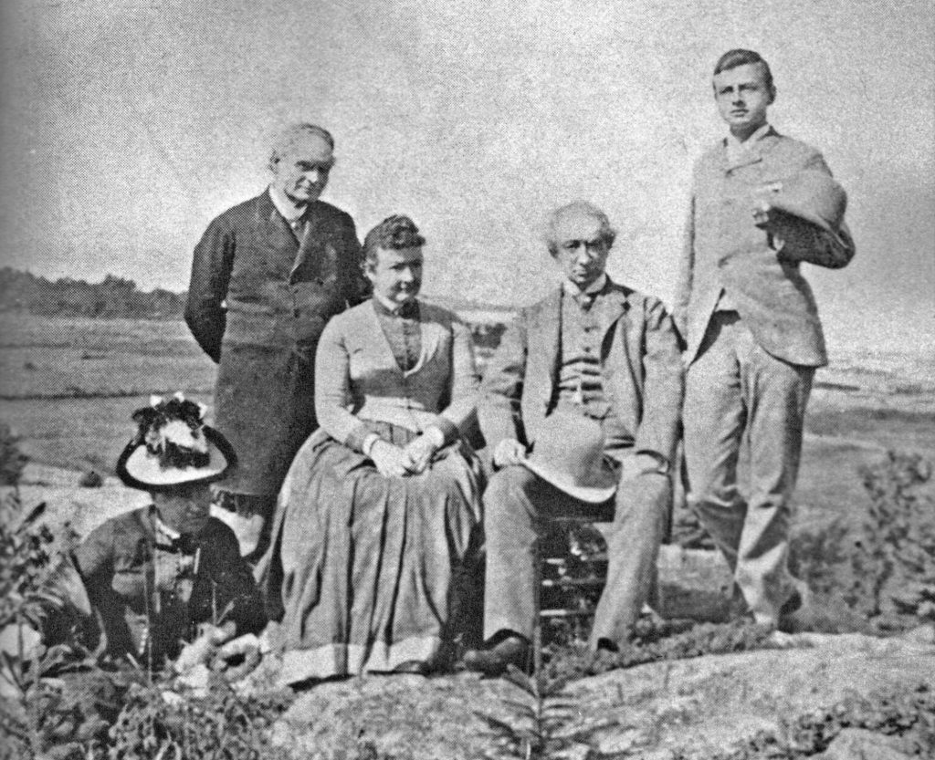A grainy, black and white photo of five adults (Sir John A. Macdonald, Lady Agnes Macdonald and members of the Tilley family) standing and seated on some rocky ground, with the Saint Lawrence River behind them.