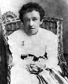 Black and white photograph of Mary Macdonald, a thin young lady leaning forward in a wicker chair, with her hands clasped on her lap. She wears a white dress with a black sash; her hair is dark and her expression vacant.