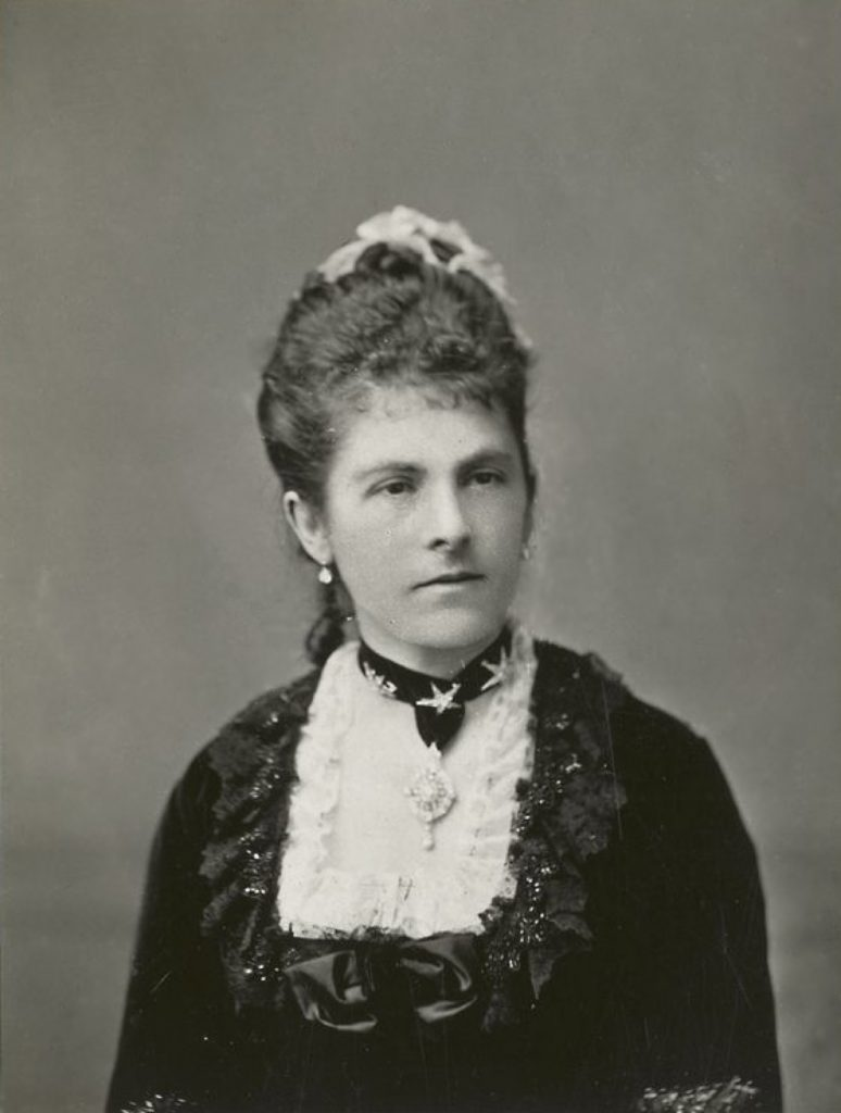 Black and white photograph of the head and shoulders of Lady Dufferin, with her hair swept up, and a formal dress with a lacy squared bodice and jewelled necklace.