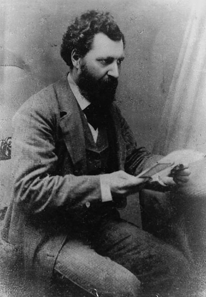 A black and white photograph of Louis Riel, seated, holding a piece of paper in his hand but not looking at it. He is bearded, has dark curly hair, and wears a three-piece woolen suit with a tie.