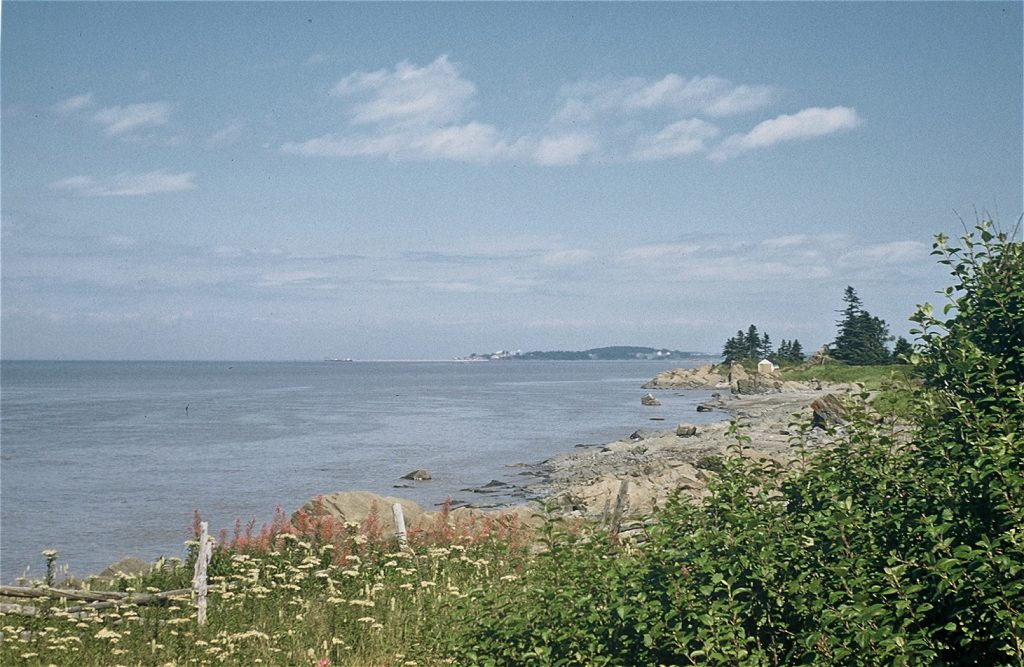 Colour photograph of a riverside scene at Rivière-du-Loup with a wooden fence in the foreground, rocks, sand, and shrubs as well as the river and some clouds in the sky.