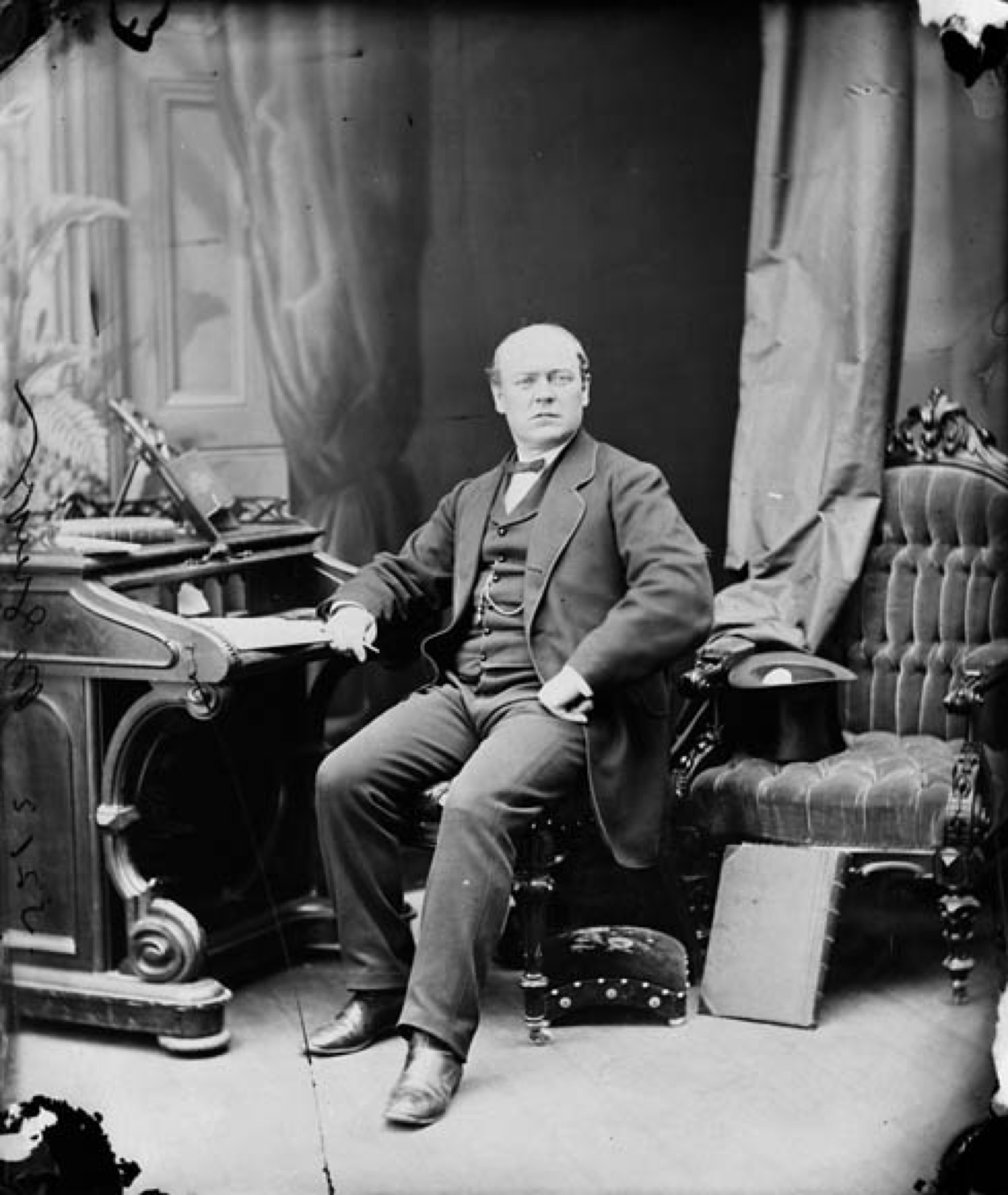 A black and white photo of Sir Thomas McGreevy, a middle-aged partially bald man sitting in an upholstered chair with one arm resting on the desk; he is facing the camera. The style of the dark formal clothing looks mid-Victorian; a top hat rests upside down on another upholstered chair next to the sitter. Draperies hang in the background, where there is a painted backdrop of a door and more drapery.