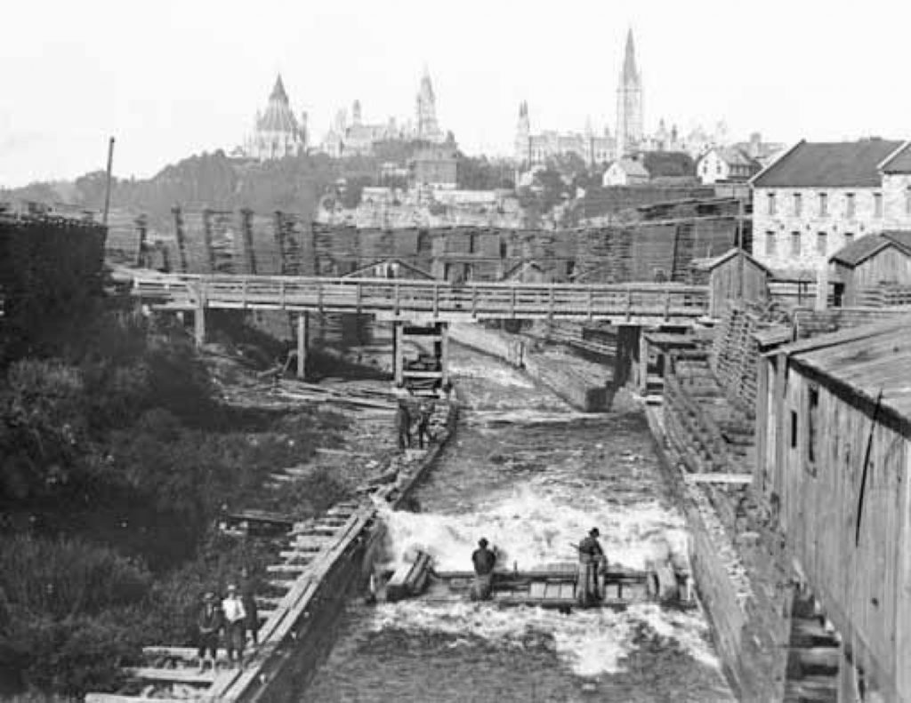 Black and white photograph taken from above a canal with Ottawa's parliament buildings in the distance; in the canal are men on a logging raft.