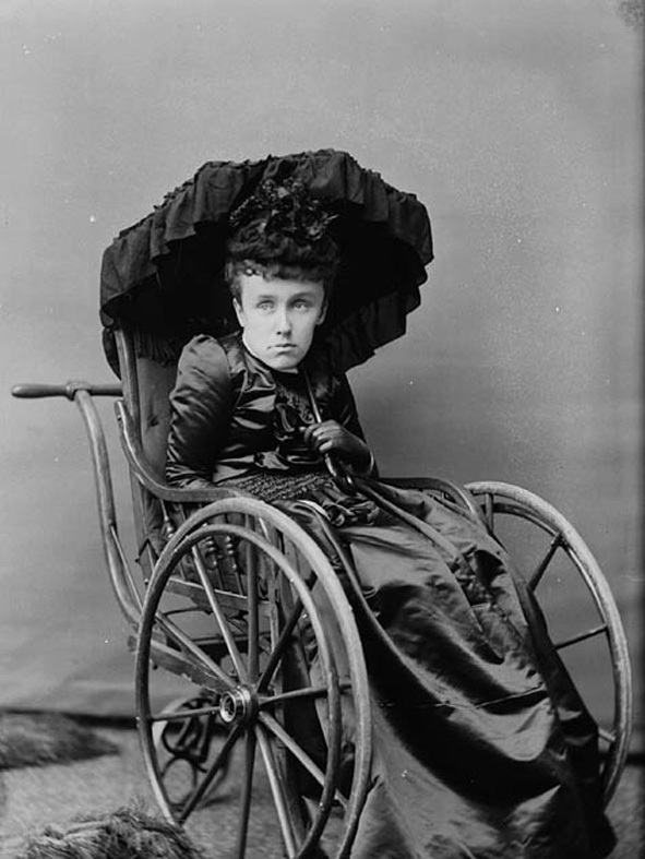Black and white photo of an adult woman (Mary Macdonald) wearing a flat, vacant expression, sitting in a 19th century style wheelchair and holding a black parasol over her head.