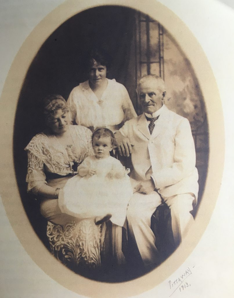 Oval sepia-toned photograph of four people (the Bate family) including an elderly man (Sir Henry Bate), a baby (his granddaughter), and two women (his wife and daughter) all dressed in white.