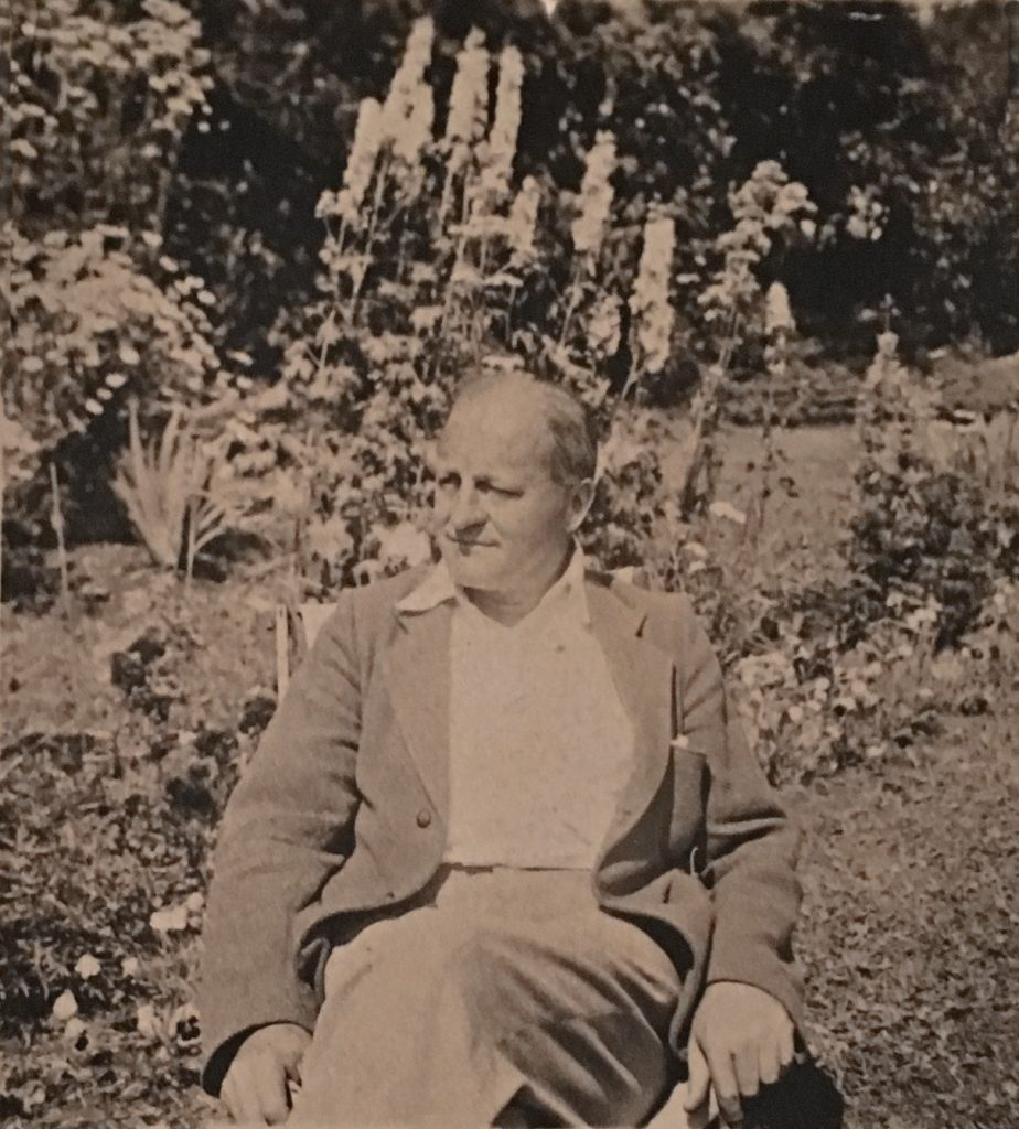 Sepia-toned photo of a middle-aged gentleman, Sir Herbert Symington, sitting on a chair outdoors with garden flowers (delphiniums) behind him.