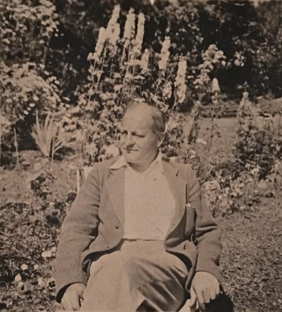 Photo aux tons sépia d'un homme d'âge moyen, Sir Herbert Symington, assis sur une chaise dans un jardin floral extérieur. Derrière lui se dressent de hauts delphiniums.