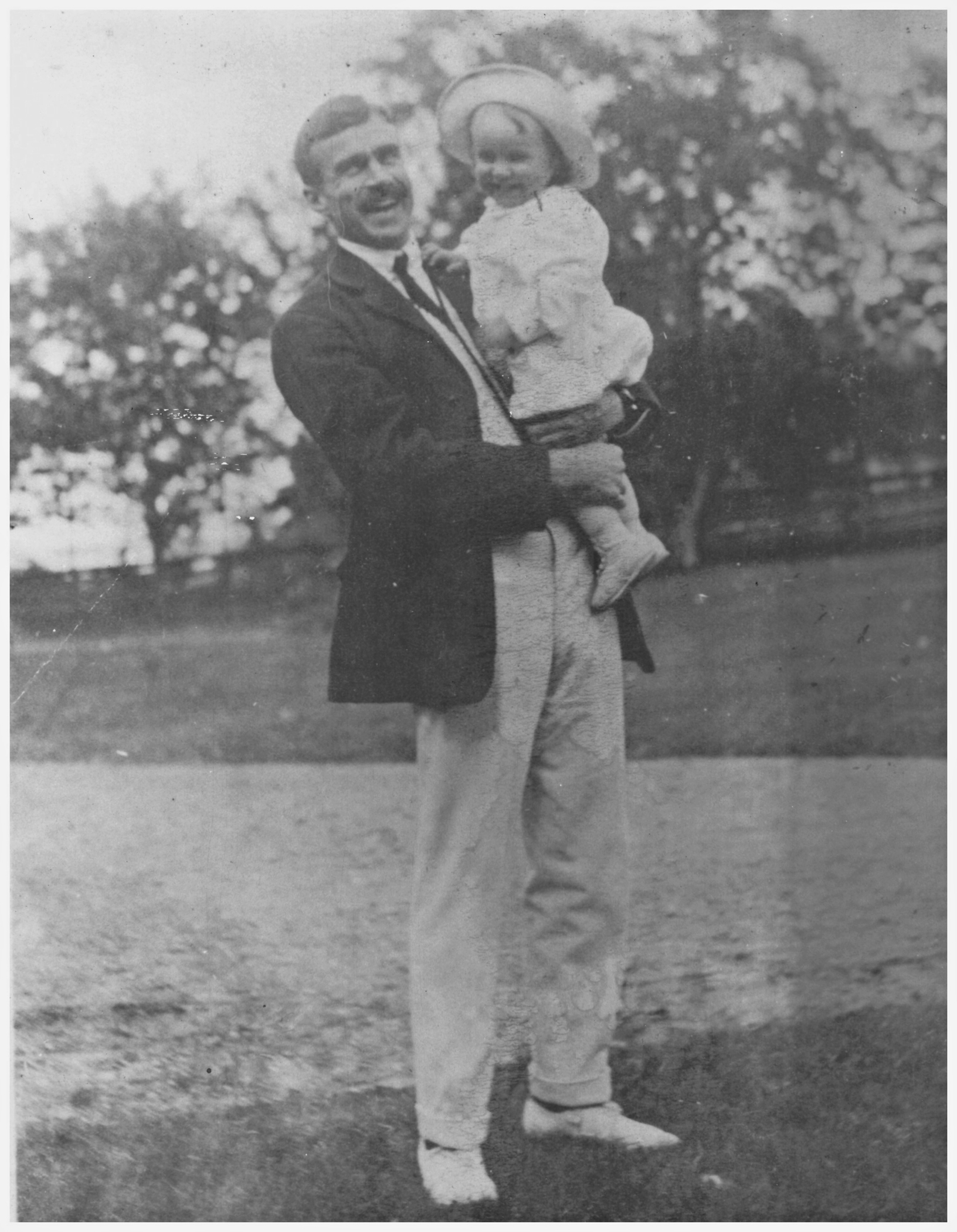 Black and white photograph of Kenneth Molson, a tall man smiling and holding a toddler, also smiling, posing outdoors with lawn and trees in the background.