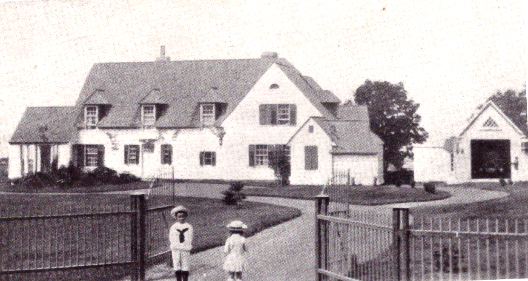 Sepia-toned photograph of an expansive house (Kenneth Molson's estate) surrounded by an iron fence with gate, and two small children in sailor suits in the foreground.
