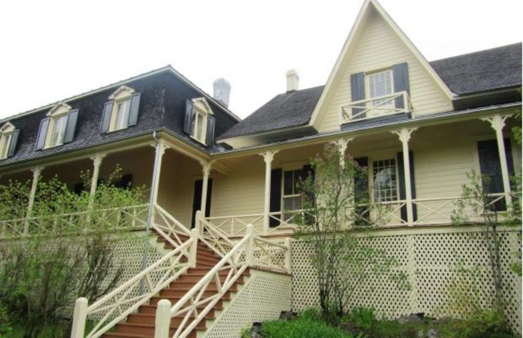 Vue frontale d'une grande maison (la villa Les Rochers) dotée d'une large véranda avec escalier, photographiée depuis la pelouse à l'avant, sous un ciel sans couleur.