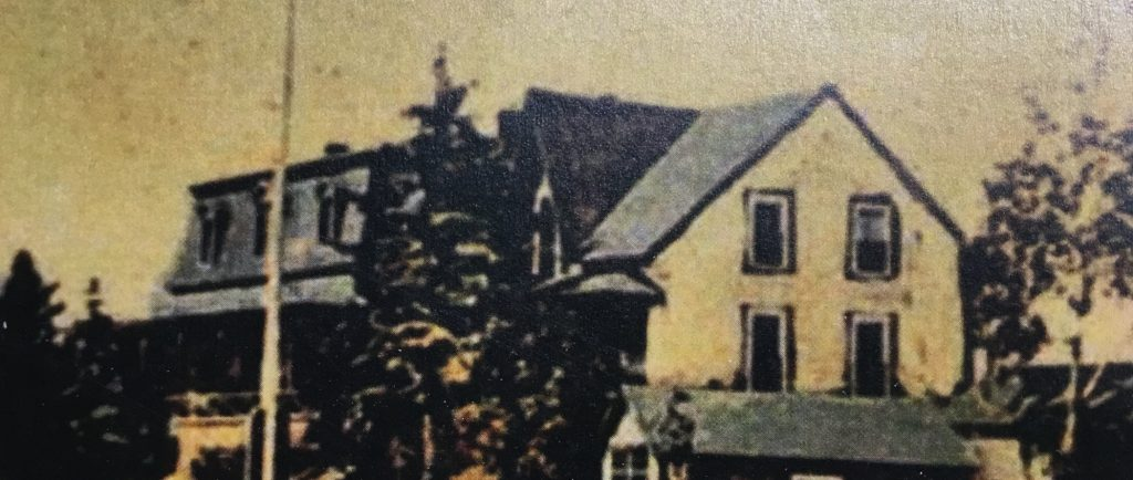 Hand-coloured (originally black and white) photograph of a large house (Villa Les Rochers) with a flagpole in front of it, and a shed attached to the side of it.