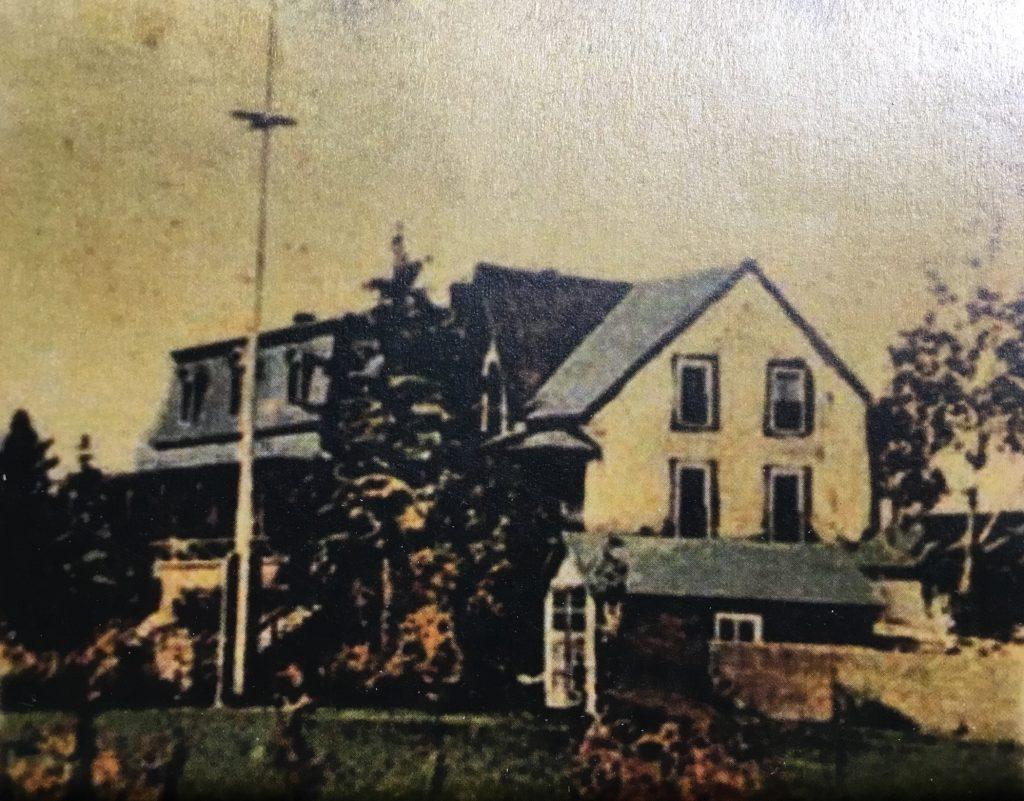 Photographie colorée à la main (à l'origine en noir et blanc) d'une grande maison (la villa Les Rochers) devant laquelle un mât de drapeau est érigé. Sur le côté de la propriété, on aperçoit une remise.
