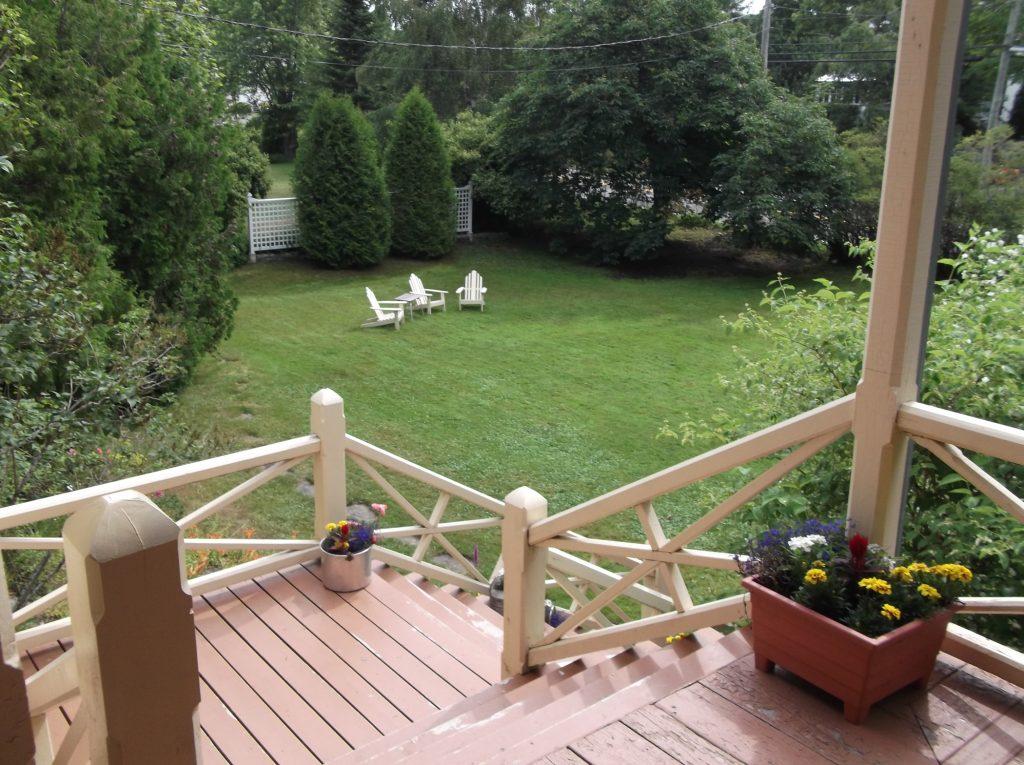 Photographie couleur montrant une pelouse bien entretenue s'étendant devant une grande véranda surplombant le paysage bordé de cèdres et de sapins. Au loin, sur le terrain, sont installées trois chaises de jardin blanches vides.