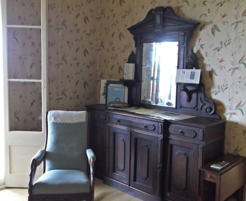 Vue intérieure d'un coin de salle à manger meublée d'une chaise capitonnée et d'un buffet en bois avec tiroirs et portes, surmonté d'un miroir, adossé à un mur recouvert de papier peint à motifs floraux.