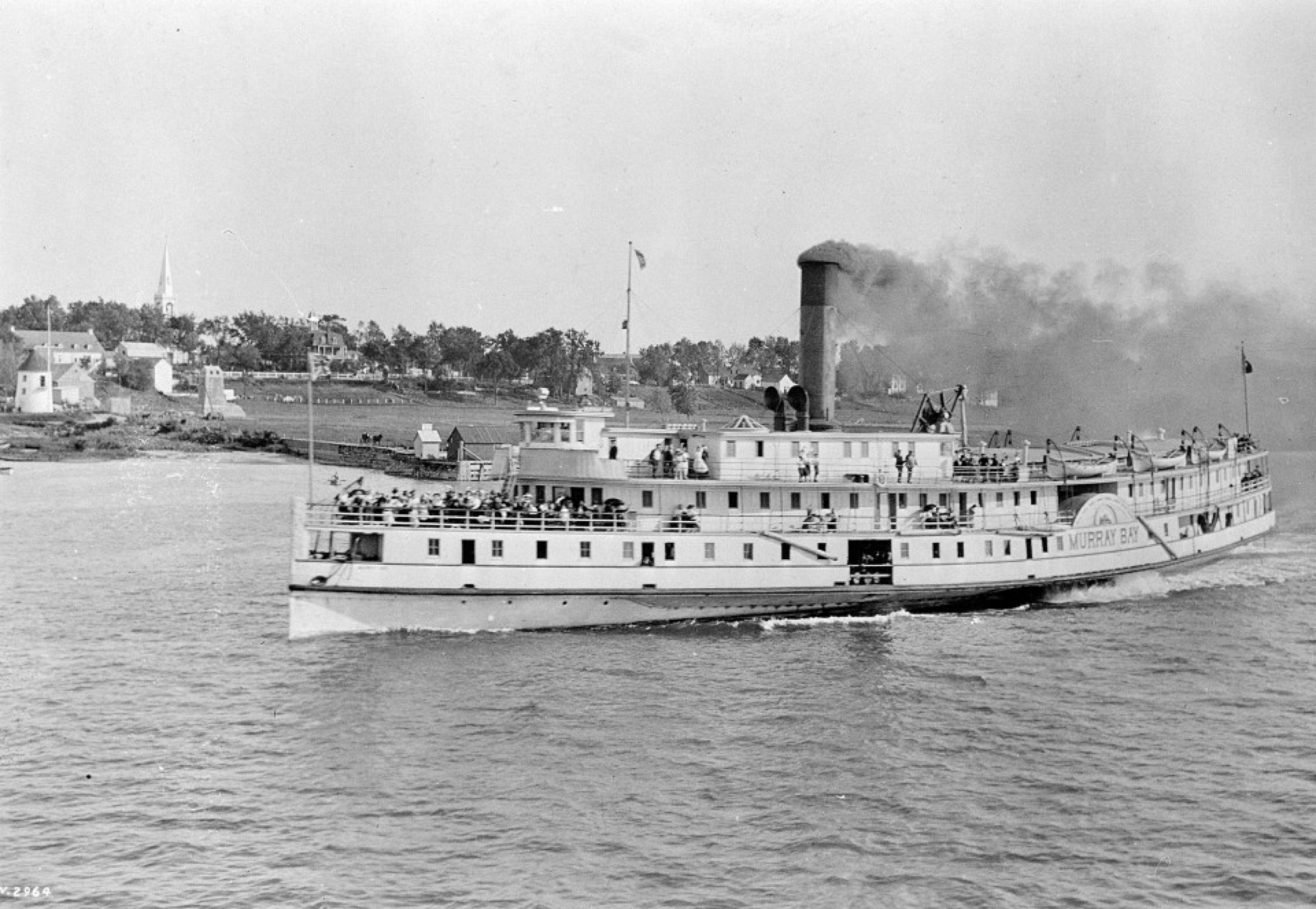Black and white image of a medium-sized steamship ferry, in transit on a large river, with black smoke coming out of the smoke stack and the front deck crowded with people.