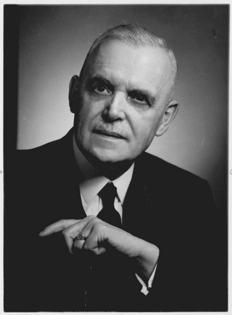 Black and white portrait of the head and shoulders and arm of Louis St. Laurent in a suit and tie, with receding grey hair, dark eyes and an authoritative expression.