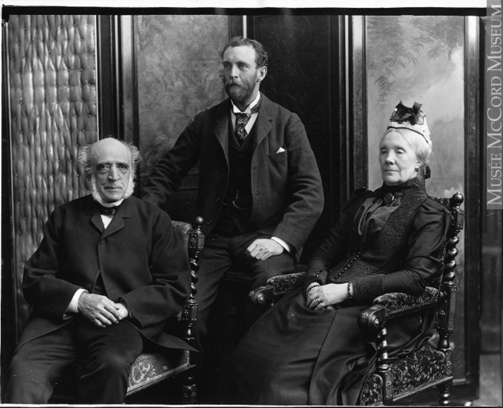 Formal black and white photo of three seated people (William C. Meredith, his wife Sofia Naters Holmes Meredith, and their son Henry Meredith), on elaborately carved chairs, the elderly couple in front, and the younger, bearded man seated behind them on a stool.