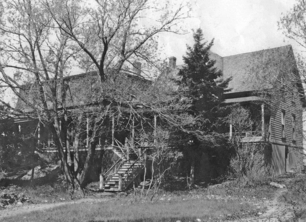 Black and white photograph of a large house (Villa Les Rochers) with a verandah spanning the front of it, a set of stairs leading up to the verandah, an overgrown deciduous tree and an evergreen tree in front.