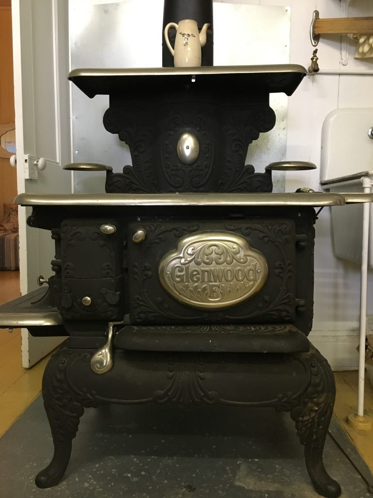 A colour photograph of a Glenwood brand cast iron cookstove, with polished metal cooking and warming surfaces. The viewer is looking at the stove from the front, facing the oven compartment's door. The stove sits on a square of tin that protects the floor. A ceramic coffeepot stands on the uppermost warming shelf of the stove.