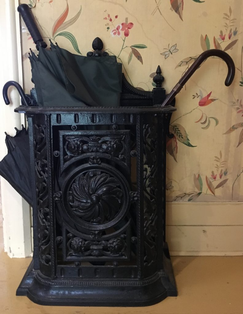 A cast-iron black painted umbrella stand about two and a half feet (62 cm) high and 18 inches (45 cm) wide, six inches (15 cm) deep. The cast iron is formed with symmetrical floral designs. The handles of two canes and one umbrella protrude from the top of the stand. Wallpaper adorns the wall behind it.